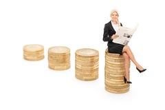 读纸的妇女供以座位在堆硬币 图库摄影