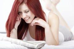 读纸的妇女在她的床 库存照片