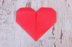 纸的红色心脏在老木白色桌上的,爱的标志 免版税库存照片