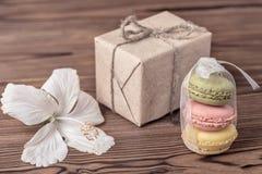 纸箱,五颜六色的macarons结块被栓的丝带,木槿开花 免版税库存照片