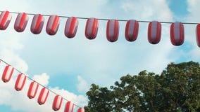 纸红白的日本灯笼垂悬在蓝天背景和树的Chochin 股票视频