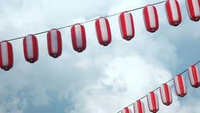 纸红白的日本灯笼垂悬在蓝色多云天空背景的Chochin 影视素材