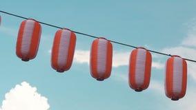 纸红白的日本灯笼垂悬在蓝色多云天空背景的Chochin 股票录像