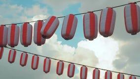 纸红白的日本灯笼垂悬在蓝色多云天空背景的Chochin 股票视频