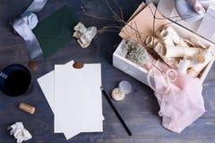 纸纸卷和珍珠在减速火箭的葡萄酒木箱 写模板的浪漫情书或婚礼邀请在木桌 库存图片
