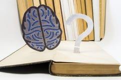 纸脑子剪影和问号在老开放医疗书 提到问题和问题的照片在脑子的研究中,  免版税库存照片