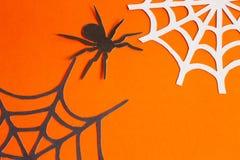 纸蜘蛛和网在橙色和黑背景的 库存图片