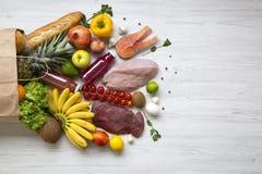 纸袋在白色木桌上的健康未加工的食物 烹调食物背景 新鲜水果,素食者,绿色平位置,不同 免版税库存照片