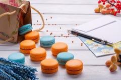 纸袋用饼干colorfool蛋白杏仁饼干和明信片与铅笔和信封 在白色木bac的可口法国点心 免版税库存图片