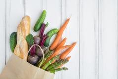 纸购物袋用新鲜面包和菜 平的位置,顶视图 免版税库存图片