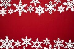 纸雪在红色背景剥落 圣诞节红色题材 免版税库存图片