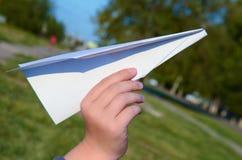 纸飞机在孩子的手上 免版税库存图片