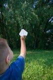 纸飞机对于在绿叶背景的儿童手和蓝天在晴朗的夏日 夏天,童年的概念,作梦 库存图片