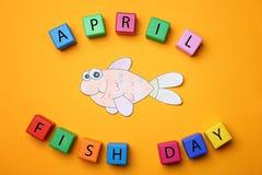 纸鱼和立方体在颜色背景 免版税库存图片