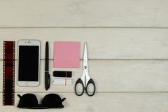 贴纸,剪刀,笔,影片,太阳镜,电话,在一张木桌上的闪存卡片 免版税库存照片