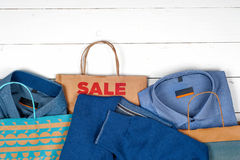 纸购物袋、人的衬衣和毛线衣在白色木背景 库存图片