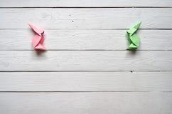 纸origami在白色板条谷仓木头的手工制造桃红色,绿色兔宝宝上背景 免版税图库摄影