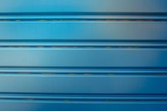 纹理或线与铁锈在蓝色不锈钢卷起门 软绵绵地集中 免版税库存图片