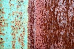 纹理被划分成一半一种生锈的两色红色和绿色老破旧的被氧化的金属,与膨胀的白色油漆,坑a的铁 库存照片