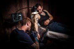 纹身花刺艺术家做纹身花刺 库存照片