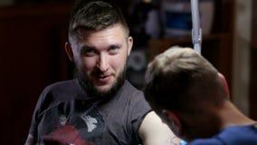 纹身花刺艺术家和一个客户的画象沙龙的 影视素材