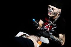 纹身花刺艺术家在纹身花刺大会工作 免版税库存图片