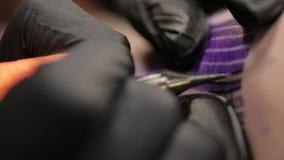 纹身花刺艺术家填装纹身花刺并且画在他的客户皮肤的线,宏观看法 股票视频