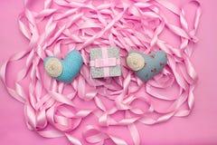 纺织品反对桃红色颜色装饰缎丝带卷的心脏礼物  免版税库存照片