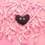 纺织品在桃红色颜色装饰缎丝带卷的背景的玩具心脏  免版税库存图片