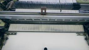 纺织品工厂机器与白色纤维一起使用,缝合它 股票录像