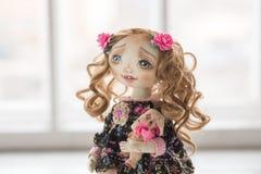 纺织品手工制造葡萄酒玩偶,在浅粉红色和蓝色纺织品礼服的长的棕色卷发画象有嫉妒的 免版税库存照片