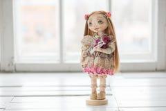 纺织品手工制造葡萄酒玩偶,在浅粉红色的纺织品礼服的长的棕色头发画象有嫉妒的有柔和的印刷品的 免版税图库摄影