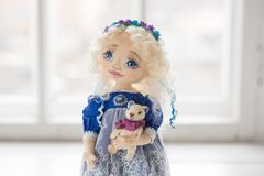 纺织品手工制造葡萄酒玩偶,在老蓝色纺织品礼服的长的金发画象有蓝眼睛的有柔和的印刷品的 库存图片
