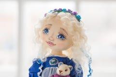 纺织品手工制造葡萄酒玩偶,在老蓝色纺织品礼服的长的金发画象有蓝眼睛的有柔和的印刷品的 免版税库存照片