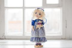 纺织品手工制造葡萄酒玩偶,在老蓝色纺织品礼服的长的金发画象有蓝眼睛的有柔和的印刷品的 库存照片