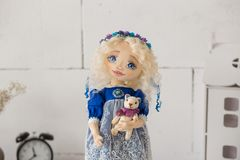 纺织品手工制造葡萄酒玩偶,在老蓝色纺织品礼服的长的金发画象有蓝眼睛的有柔和的印刷品的 免版税库存图片