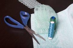 纺织品的装饰与鞋带磁带的 黑暗的表面的毛巾基于 对此说谎鞋带丝带,穿线卷轴和剪刀 库存图片