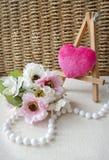 纺织品桃红色心脏、花和项链在褐色wickered背景 看板卡日s华伦泰 库存图片