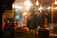 纽伦堡,德国- 2013年12月22日:时髦的推销员在晚上在圣诞节市场,纽伦堡,德国卖香肠 库存图片