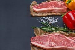 纽约与胡椒、盐和迷迭香backgr的striploin牛排 库存照片