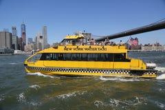 纽约在布鲁克林大桥下的水出租汽车 库存照片