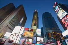 纽约时代广场的升在晚上充分明亮的商业屏幕 库存照片