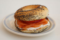 纽约样式百吉卷用熏制鲑鱼,乳脂干酪、蕃茄、葱和雀跃 免版税图库摄影
