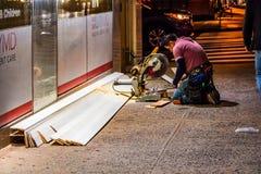 纽约,东部第46条街道,曼哈顿- 2017年11月1日:建筑工人使用一把锯削减门面片断在 图库摄影