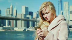 纽约,反对曼哈顿和布鲁克林大桥游人背景一件桃红色外套的键入在您的智能手机的 股票视频