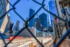 纽约,纽约- 2013年12月27日:与纽约的都市风景 世界贸易中心一号大楼通过篱芭 免版税库存照片