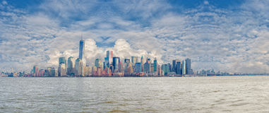 纽约,纽约- 2013年12月28日:哈得逊河和街市曼哈顿地平线, NYC有多云蓝天的风景全景 免版税库存照片