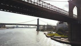 纽约,美国的鸟瞰图 直升机飞行在对曼哈顿桥梁的布鲁克林大桥下通过East河 股票录像