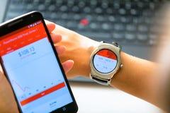 纽约,美国- 2015年8月20日:的女商人看起来在她的smartwatch和智能手机的股市行情 免版税库存照片