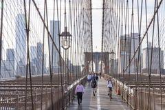 纽约,美国- 06-03-2016 -许多步行者和骑自行车者许多围拢的布鲁克林大桥的上甲板的钢c 免版税图库摄影